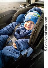 Cute smiling boy in hat sitting in car child seat - Portrait...