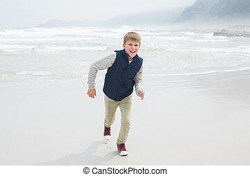 Cute smiling boy running at beach