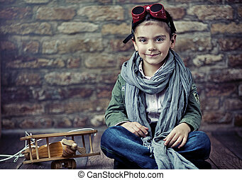 Cute smiling boy with wooden plane - Cute smiling boy...