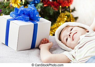 Cute smiling child boy in Santa Claus hat with new year present or christmas holiday gift box