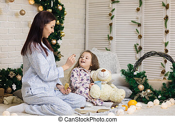 Cute smiling child girl with her mother play with teddy bear
