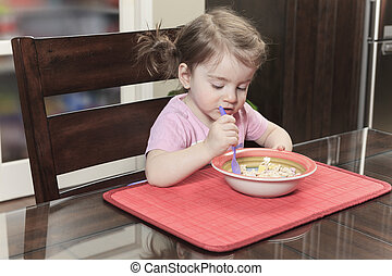cute smiling girl eating cereal with the milk in the kitchen