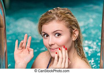 cute smiling girl posing in a swimming pool