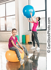 Cute smiling girl sitting on fitness ball while mother exercising