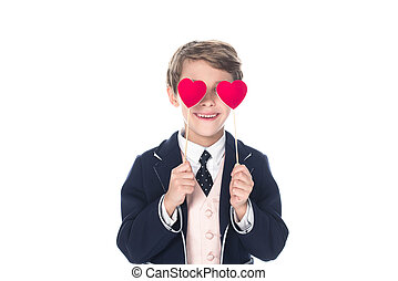 cute smiling little boy in suit holding red hearts on sticks isolated on white