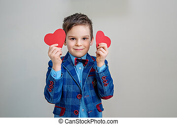 cute smiling little boy in suit holding red hearts on sticks