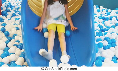 Cute smiling little girl having fun on slide in playroom.