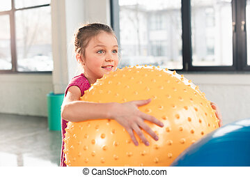 Cute smiling little girl holding fitness ball and looking away