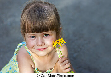 Cute smiling little girl holding yellow flower