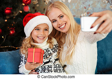 Cute smiling little girl  in Santa's hat holding gift box while her mother taking selfie on smartphone