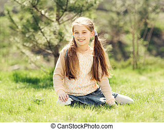 cute smiling little girl sitting on the grass