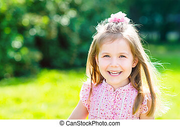 Cute smiling little girl with long blond hair, outdoor portrait in summer day