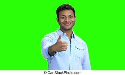 Cute smiling man showing thumb up gesture. Handsome Indian...