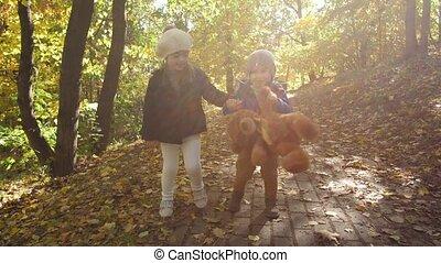 Cute smiling siblings walking hand in hand outdoor