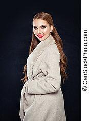 Cute smiling woman in beige coat posing on black background