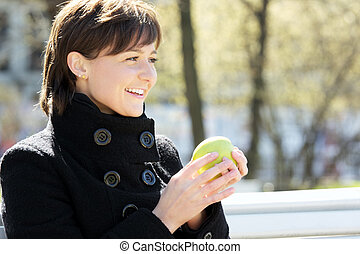 Cute smiling woman in park with apple