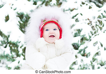 Cute smling baby girl in a warm white jacket sitting next to a C