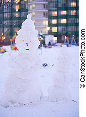 cute snowy snowman in the evening at the christmas city with nobody