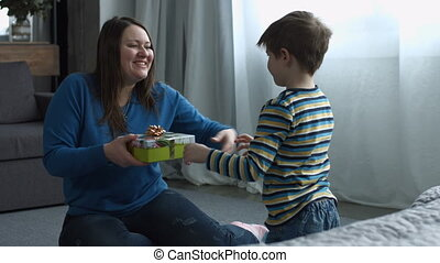 Cute son giving gift box to mom on Mother's Day