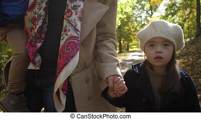 Serious little girl with down syndrome walking hand with mother through autumn park. Midsection of loving mom holding toddler son on her arms and leading special needs daughter by hand in nature