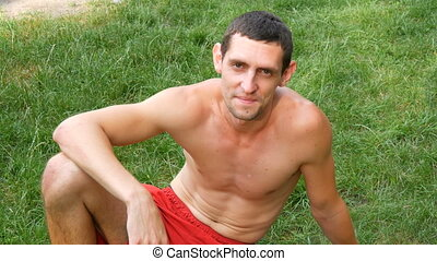 Cute sporty young man with a naked torso sits on the grass...