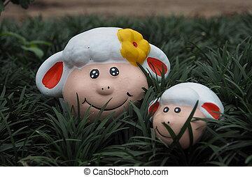 Cute statue sheep on grass.