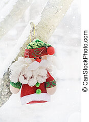 cute stuffed toy santa claus on the background of snow-covered branches of the christmas tree. Santa Claus doll. copy space