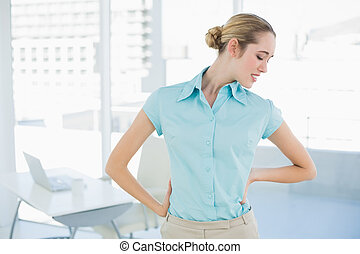 Cute suffering businesswoman holding her injured back