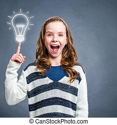 Cute surprised girl pointing at light bulb.