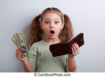 Cute surprising kid girl holding wallet and dollars with...