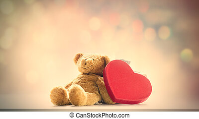cute teddy bear and beautiful heart shaped toy on the fairy lights bokeh background