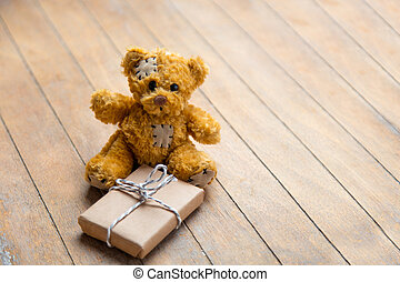 cute teddy bear holding beautiful small gift on the wonderful wooden brown background