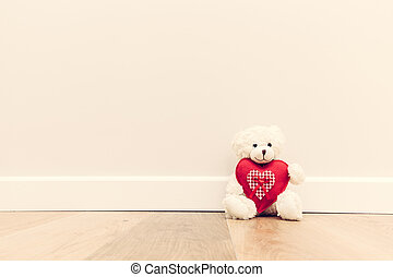 Cute teddy bear with big red plush heart. Sitting on wooden ...