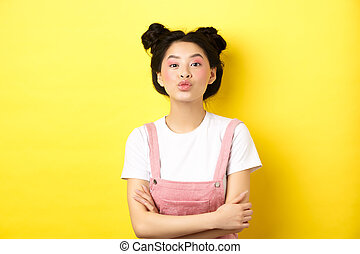 Cute teen asian girl pucker lips for kiss, cross arms on chest and look romantic at camera, yellow background