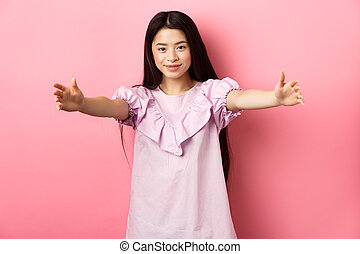 Cute teen asian girl stretch out hands for hug, want to cuddle, friendly greeting you, standing on pink background