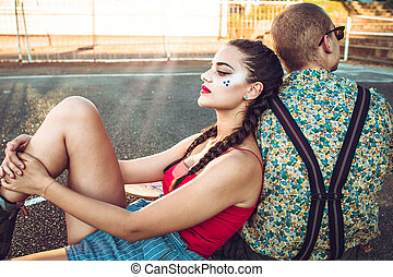 Cute teen couple sit outside. Girl looks upset about something