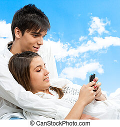 Cute teen couple socializing with smart phone outdoors.