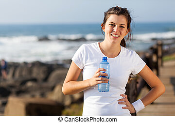 cute teen girl drinking water after workout