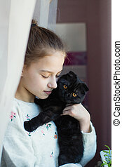 Cute teen girl holding a kitten in her arms.