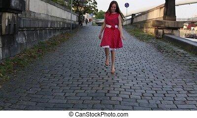 Cute teen girl in red dress runs