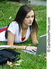 Cute teen girl laying down on the grass studying with her...