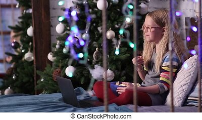 Cute teen girl watching funny cartoons on laptop