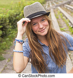 Cute teen girl wearing a hat, outdoors in the park (square series)