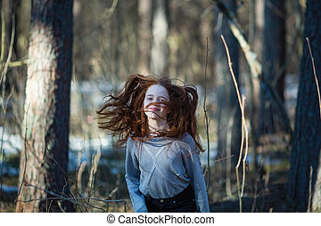 Cute teen girl with fiery red hair posing in the pine park for a photo shoot.