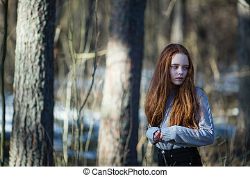 Cute teen girl with fiery red hair posing in the pine park for a photoshooting.