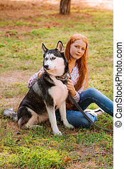 Cute teen girl with red long hair walks with her husky breed dog in the autumn park.