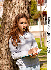 Cute teen girl writes with a pen in a notebook near in a park. Selective focus