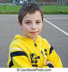 Cute teenage boy in a yellow hoodie in the playground