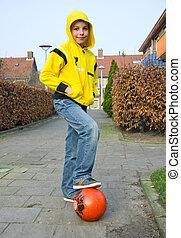 Cute teenage boy with a ball on the street