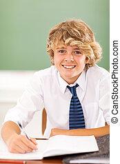 teenage boy writing in class